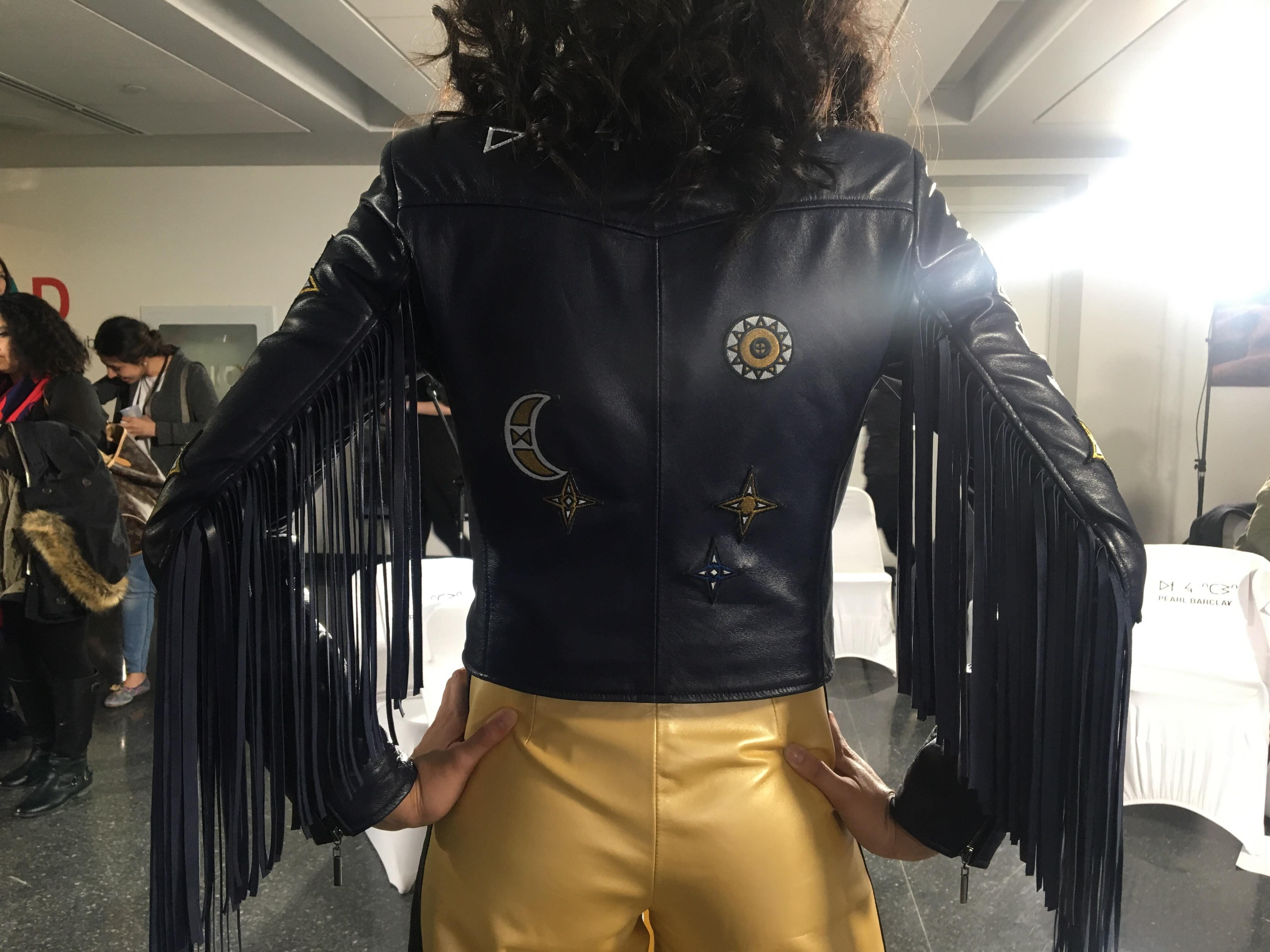 A person wearing a black jacket and gold pants.