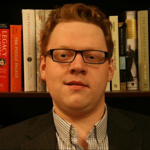 A close up photo of Neil Robert Moss, with books on a shelf visible in the background.